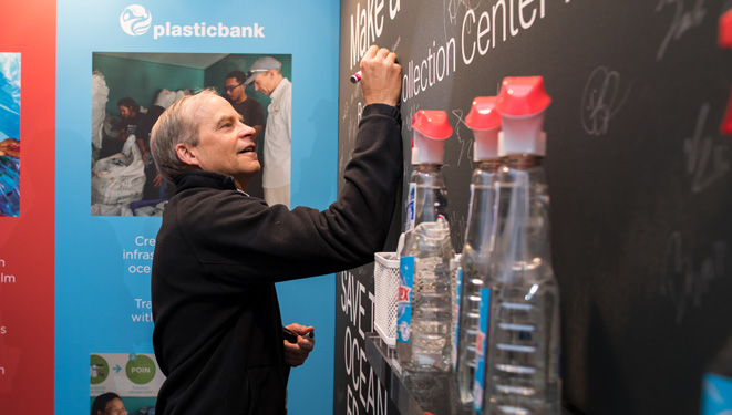 Fisk Johnson signing a promise wall to end ocean plastic at Greenbiz