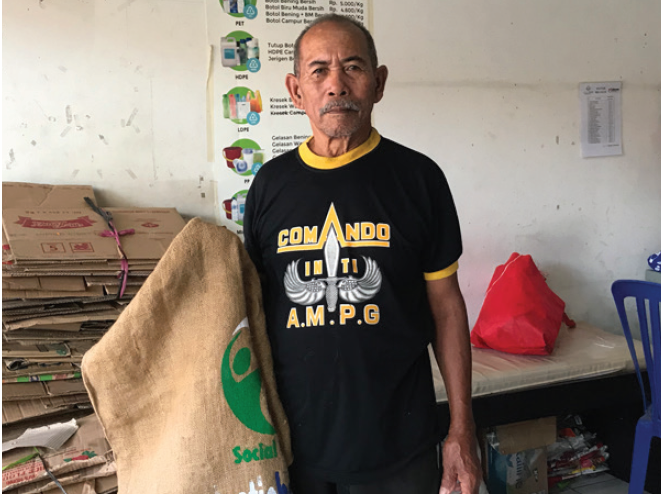 Man holding plastic bank recycling collectors bag.