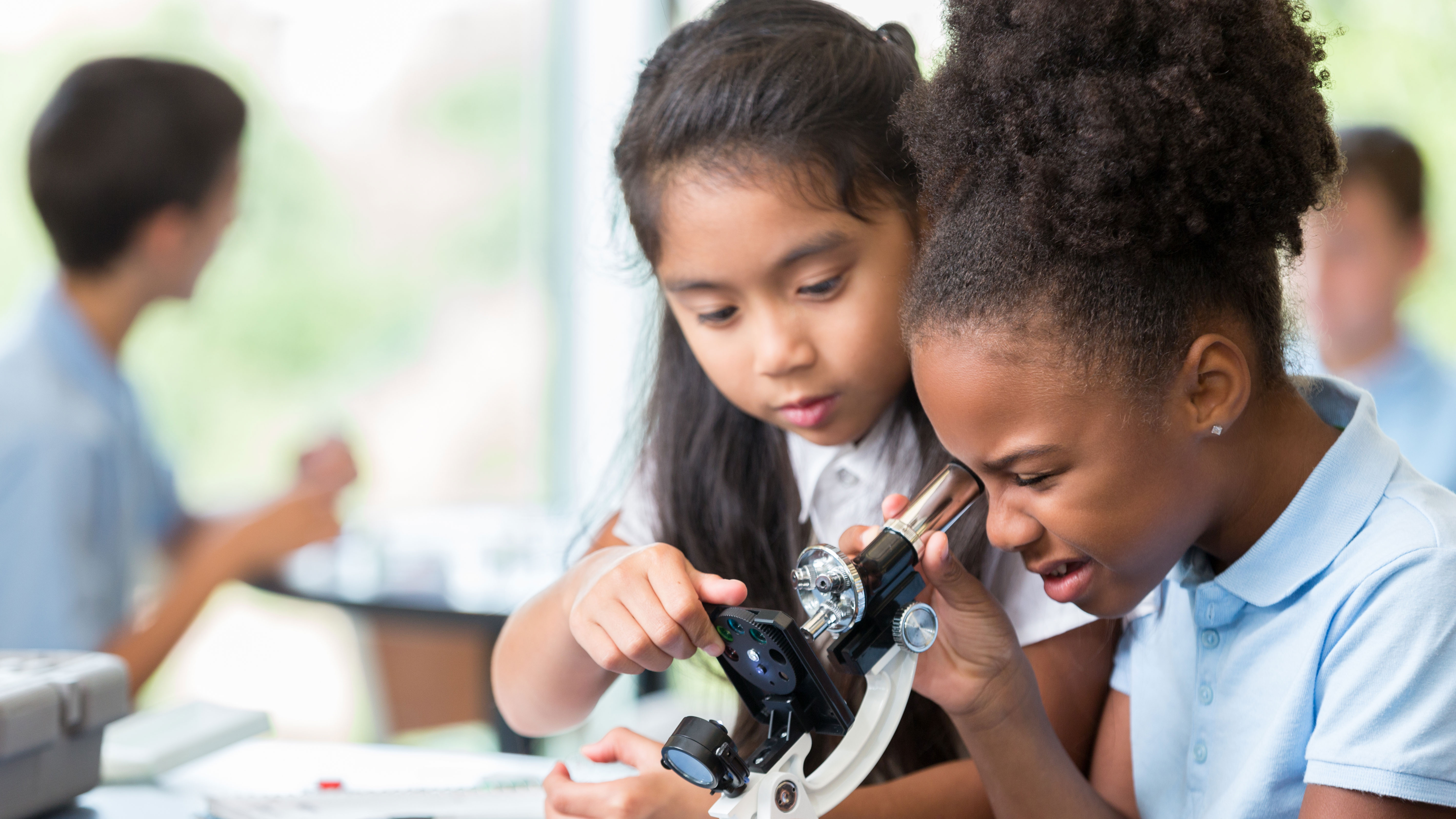Young girls in science class looking into a microscope